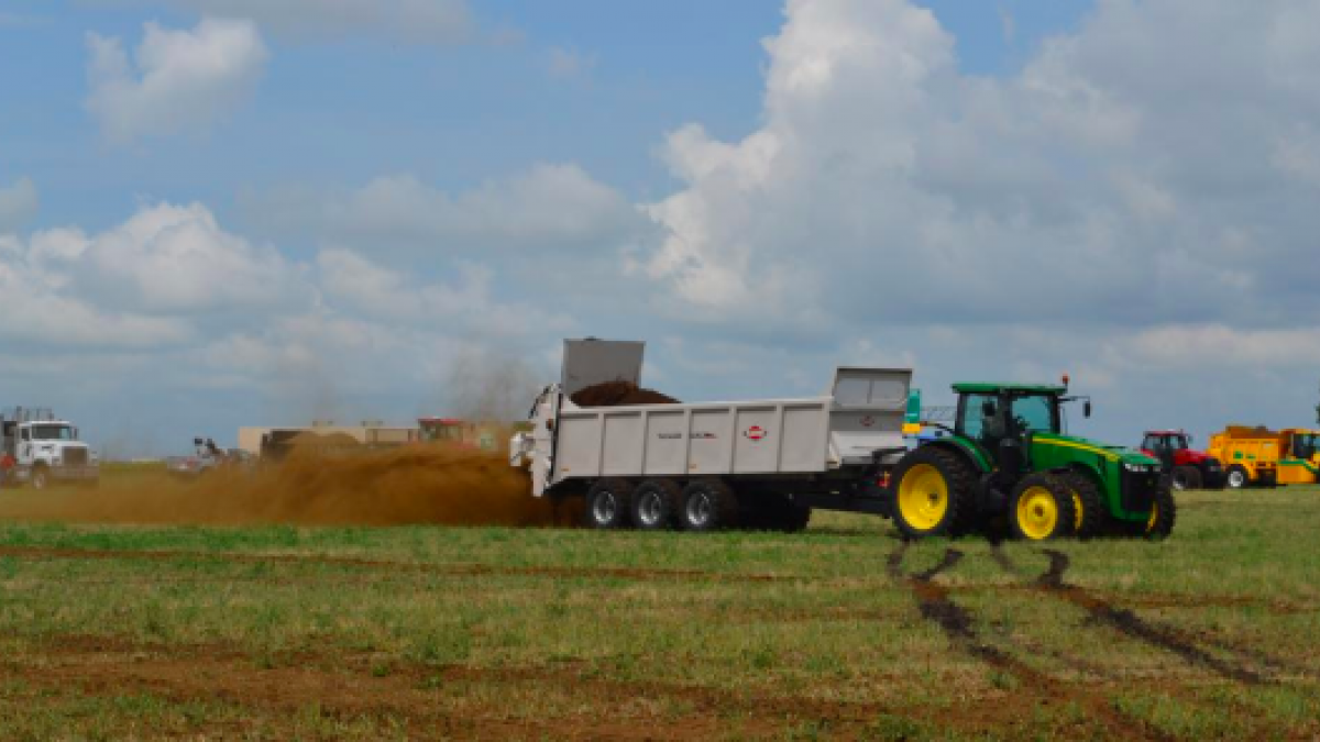 A tractor dumping manure.
