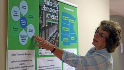 Cheryl Burkhart-Kriesel pointing to bulletin board