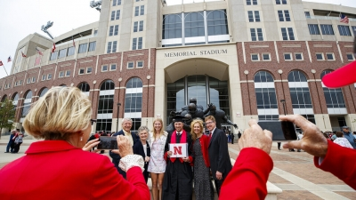 a graduate getting his picture taken in front of memorial stadium during graduation