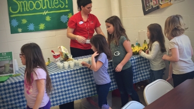 Nebraska Extension Educator Kayla Colgrove shares smoothie samples with Tri County Public Schools students during a recent farmers market held at the school.