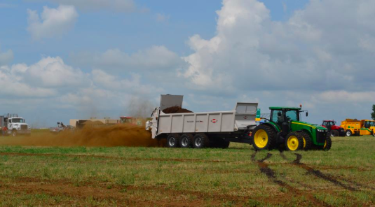 A tractor dumping manure. Links to larger image.