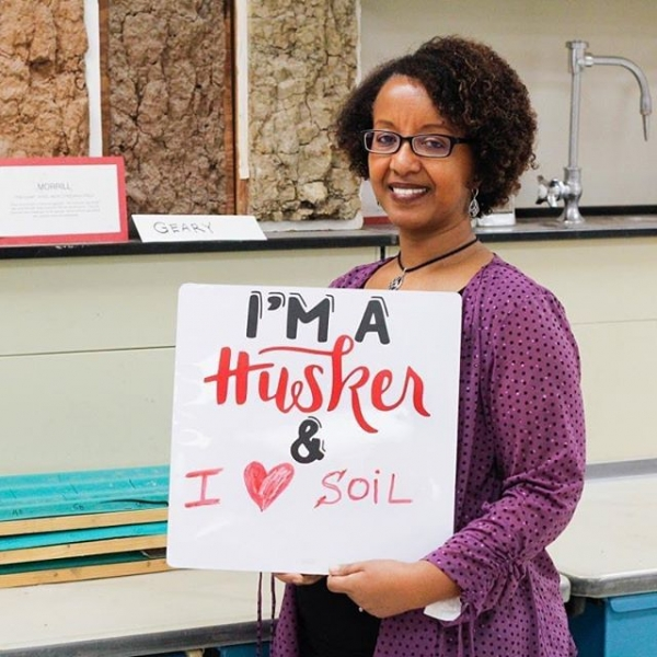 Martha holding I'm a Husker and I love Soil Sign